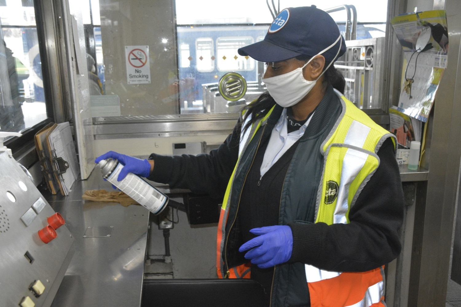 A rail station employee wears a mask and gloves as she disinfects her workspace at the start of her shift