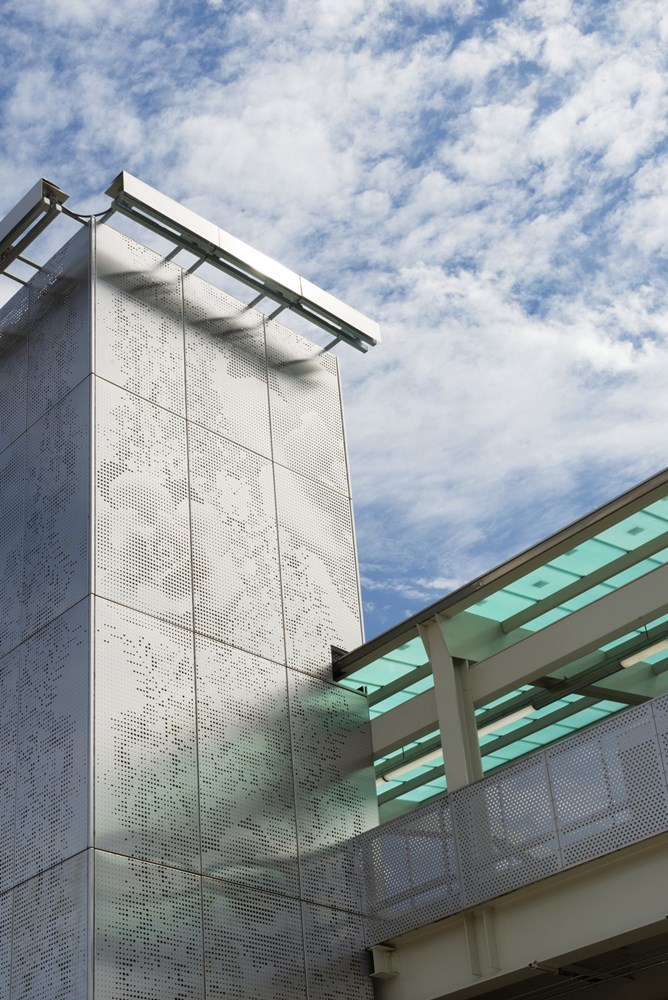 Close-up view of perforated steel wrap on elevator towers featuring a floral pattern