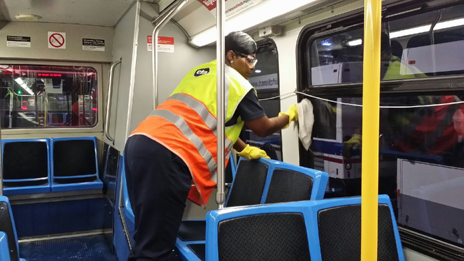 Female CTA worker shown cleaning interior of bus.