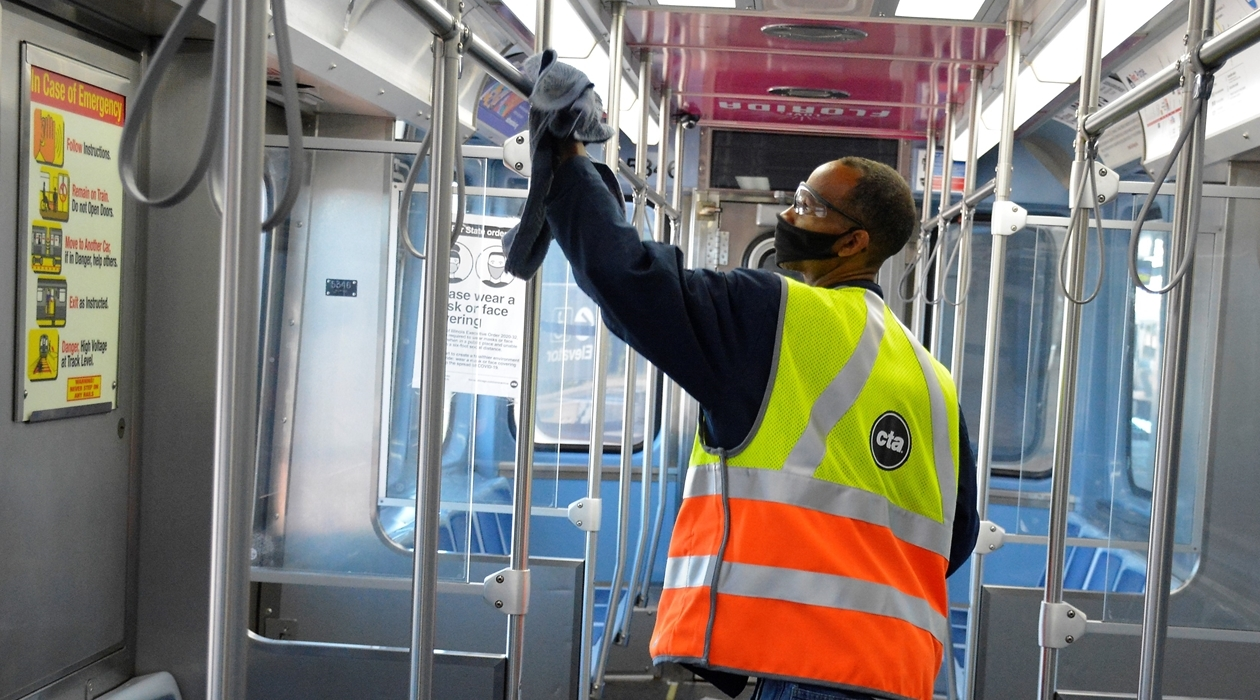 CTA employee disinfecting interior surfaces of a rail car